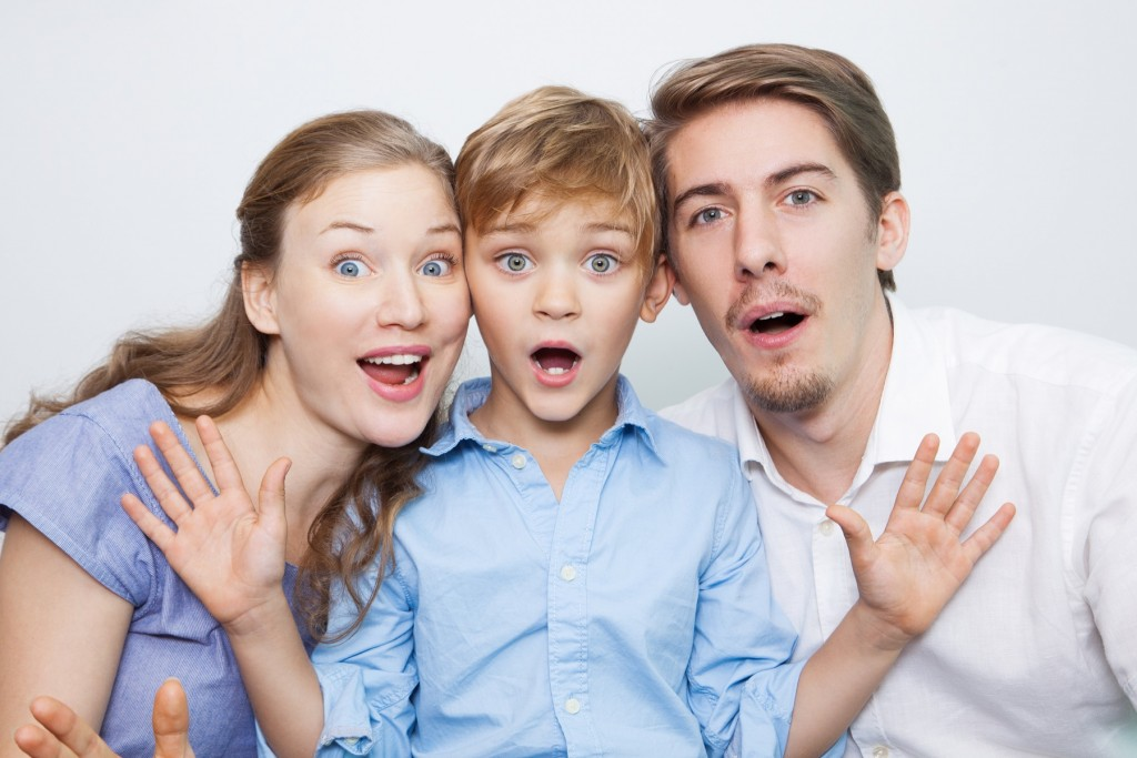 Portrait of surprised young Caucasian family with little son looking at camera and smiling with mouth open